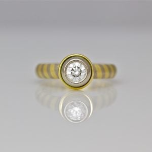 Diamond set in 18ct gold, on diagonal stripe ring.