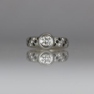 Diamond rub-over set in Platinum with pave set ring