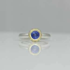 Sapphire framed with diamonds engagement ring