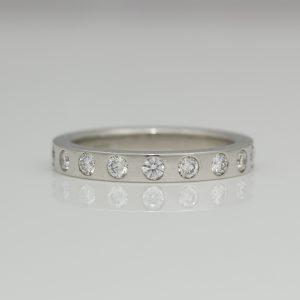 Flat profile ring with flush set diamonds.