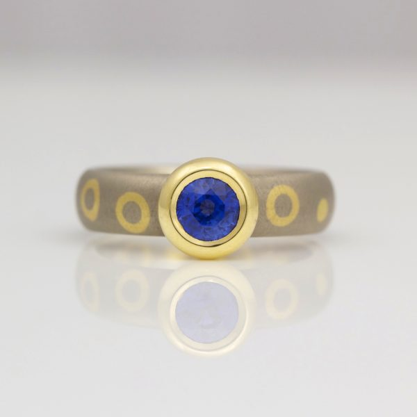 Sapphire rub-over set in yellow gold on white gold dot and circle ring