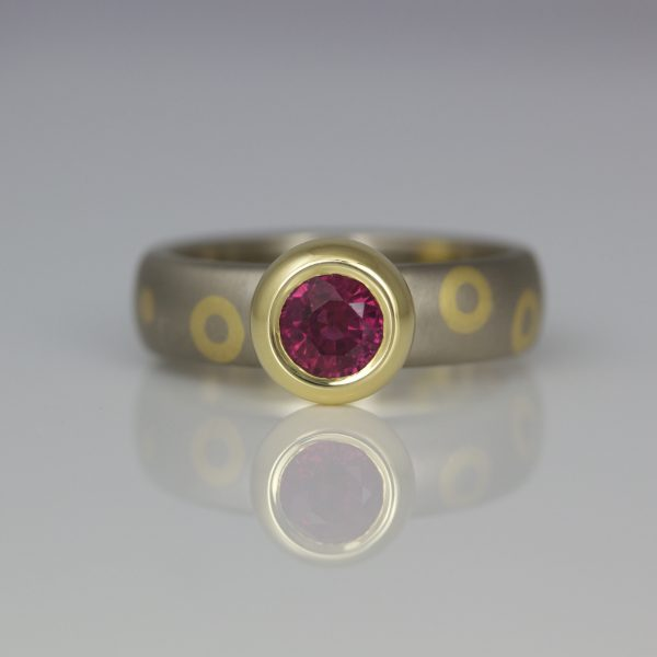 Modern yellow & white gold ruby ring rub-over set, with dots & circles