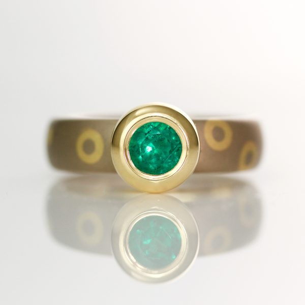 Rub-over set emerald on 18ct dot and circle ring