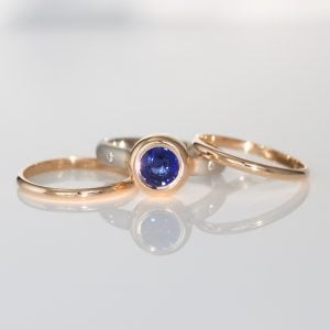 Blue sapphire, rub-over set in rose gold with platinum triple ring