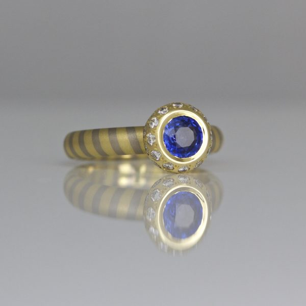 Sapphire framed with diamonds on 18ct diagonal striped band