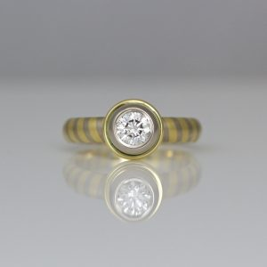 Diagonal stripe ring with solitaire diamond rub-over set